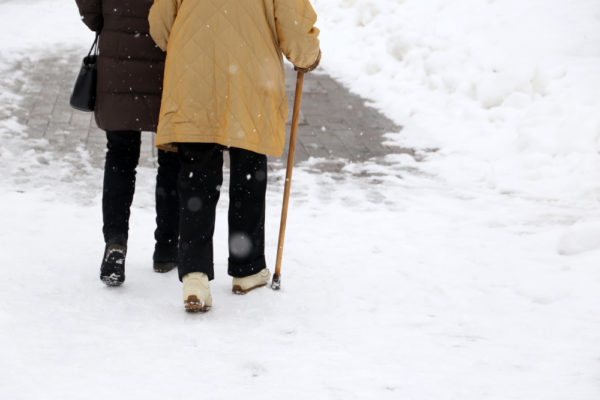 older couple with joint pain walking in the snow
